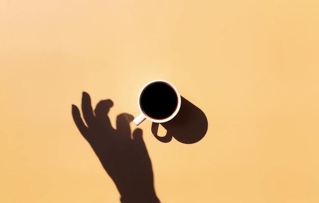 Tazza bianca e piattino di caffè espresso nero dalla vista dall'alto con ombra di sole e mano che tiene o tocca la tazza su fondo in terracotta beige giallo. foto di alta qualità