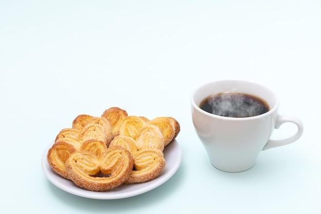 Tazza bianca di caffè nero caldo fumante o cioccolata calda e biscotti a forma di cuore appena cucinati su sfondo azzurro
