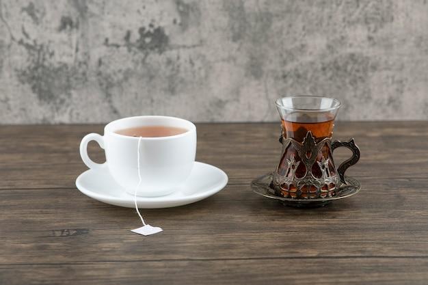 Una tazza bianca di gustoso tè caldo con una tazza di vetro su un tavolo di legno.