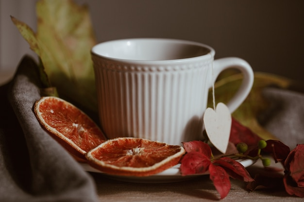Bianco tazza di tè in autunno ancora in vita
