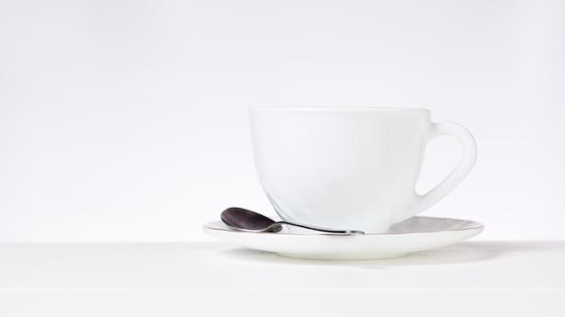 Una tazza bianca per tè o caffè e un cucchiaio di metallo su un tavolo bianco su sfondo grigio. piatti per tè e caffè.