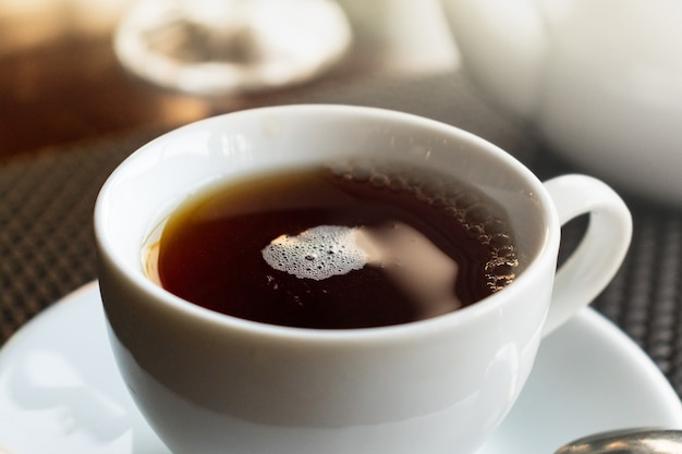 Tazza di tè bianco su un piattino bianco con un cucchiaio