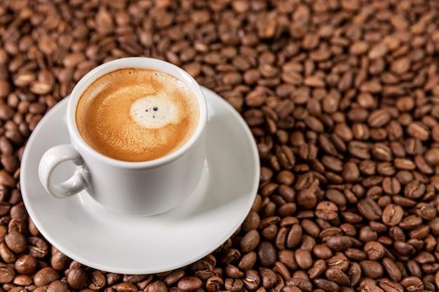 Tazza bianca con caffè aromatico su grani sparsi.