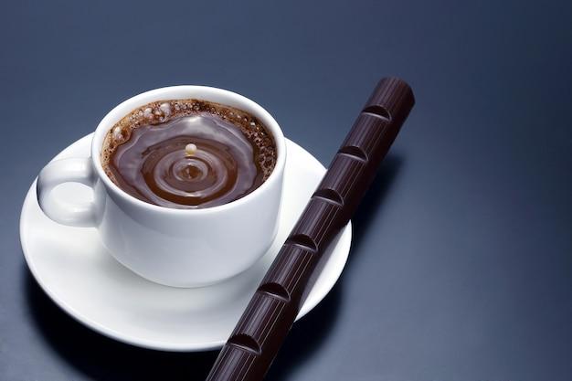 Tazza bianca con caffè nero e cioccolato sul piattino