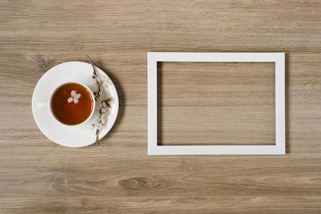 Una tazza bianca con tè nero e un rametto di fiori di melo e una cornice bianca su uno sfondo di legno. mocap e su protranstva