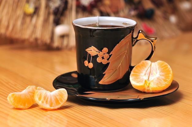 Tazza bianca con brillante stampa floreale e una fetta di limone su fondo in legno