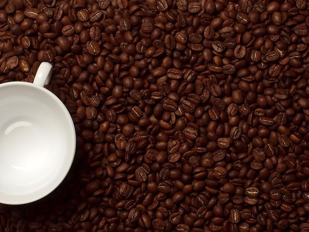 Tazza bianca con chicchi di caffè. caffè in chicchi macro. trama di sfondo astratto. trama di chicchi di caffè. sfondo alimentare di chicchi di caffè