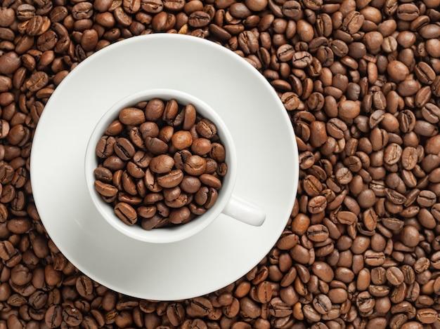 Tazza bianca con chicchi di caffè, stare sui chicchi di caffè in soft focus, vista dall'alto, copia dello spazio