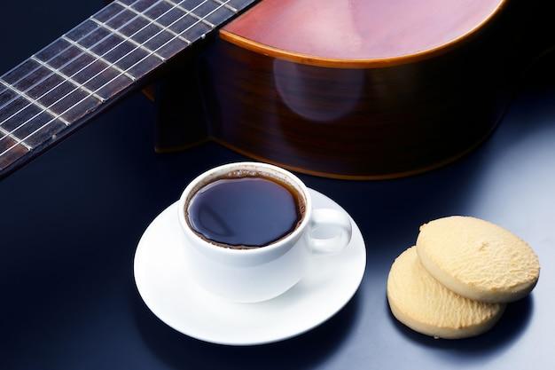 Tazza bianca con caffè e biscotti in sottofondo chitarra acustica