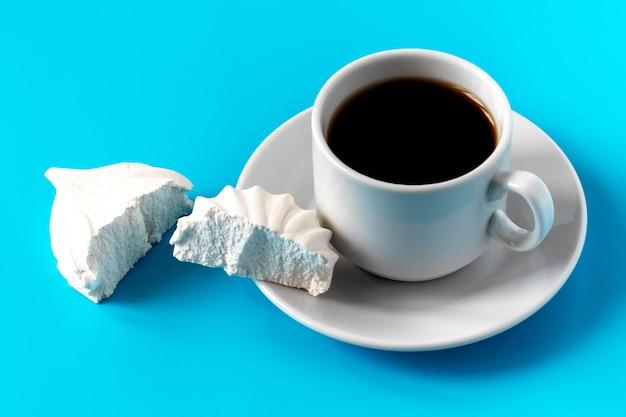 Una tazza bianca con caffè su un piattino e un marshmallow alla vaniglia bianco spezzato in due metà. pausa caffè e dolce dessert