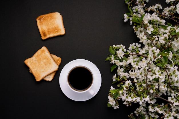 Tazza bianca con caffè e pane tostato, fiori di primavera, ramo di ciliegio su uno sfondo scuro.