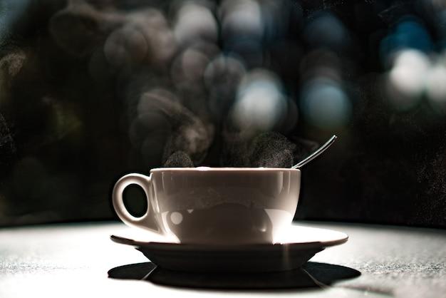 Tazza bianca con liquido caldo e vapore nero su sfondo sfocato. cucchiaino in una tazza