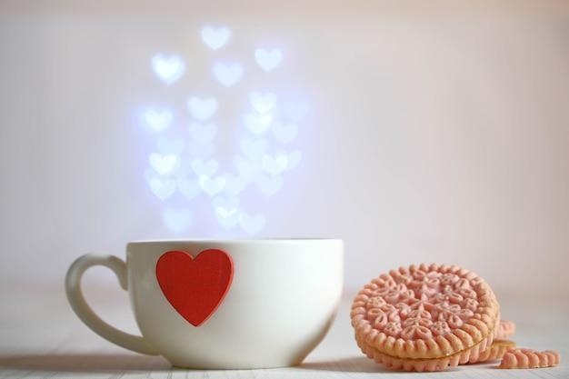Tazza bianca con cuore rosso, biscotti e fontana di luci