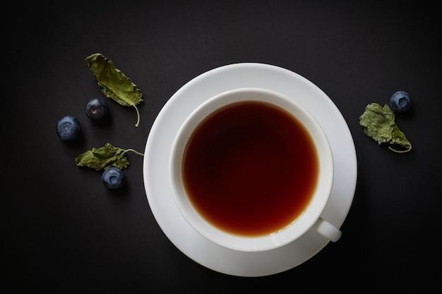 Tazza bianca con tè, mirtilli e foglie di menta secca su uno sfondo scuro