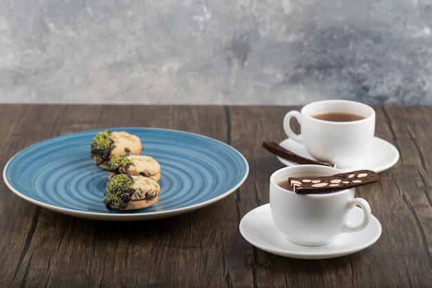 Tazze bianche di tè caldo con la torta affettata disposta sulla tavola di legno.