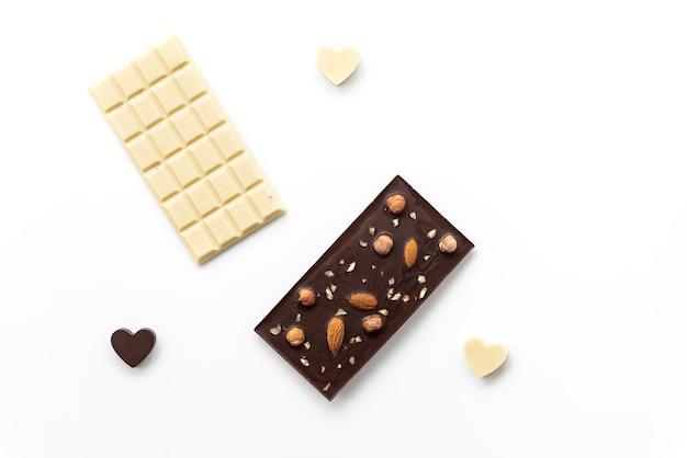 Tavolette di cioccolato bianco e fondente con cuori su superficie bianca.