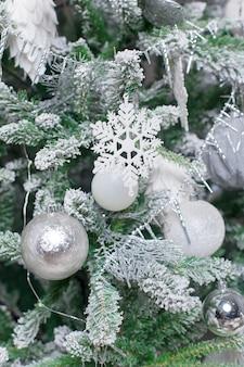 Sfera decorativa bianca sull'albero di natale sul fondo del bokeh di scintillio con neve vaga.