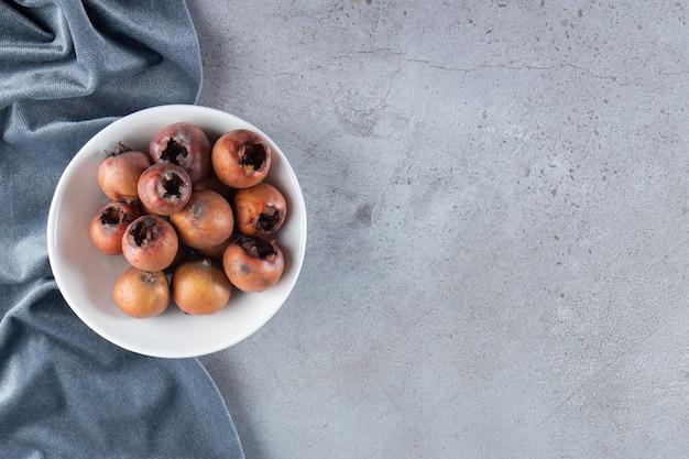 Piatto fondo bianco di frutta fresca di nespola su fondo di pietra.