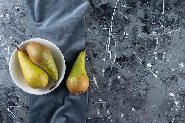 Piatto fondo bianco di pere mature fresche su fondo di marmo.