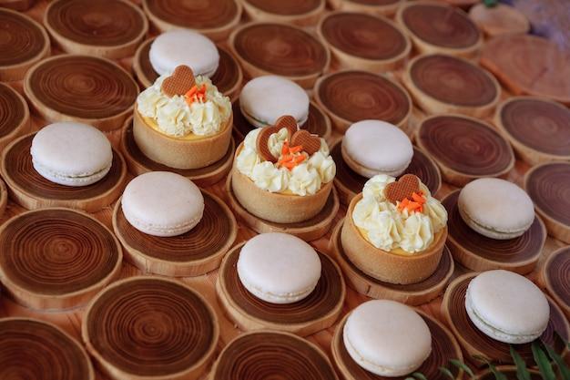 Amaretti bianchi delicati e umili su uno sfondo di legno il tono pastello della crema all'interno del...