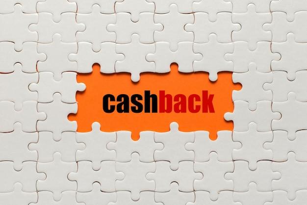 Dettagli bianchi del puzzle sull'arancia e sulla parola cashback.