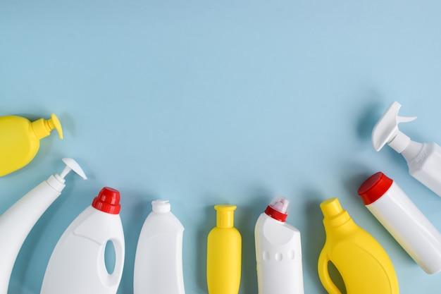 Bottiglie di detersivo bianche su una superficie blu