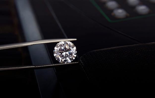 Diamanti bianchi su pinze e sfondo nero