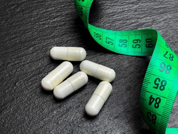 Pillole dietetiche bianche accanto a un nastro di misurazione