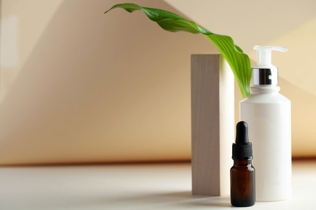Dispenser bianco con cosmetici e siero per la pelle con spazio per il tuo logo spa concept skin care copy space