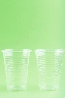 Bianco monouso tazze, piatti, forchette, coltelli su sfondo verde chiaro close-up -