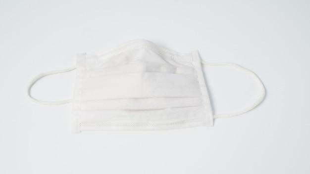Maschera facciale monouso bianca su sfondo bianco.