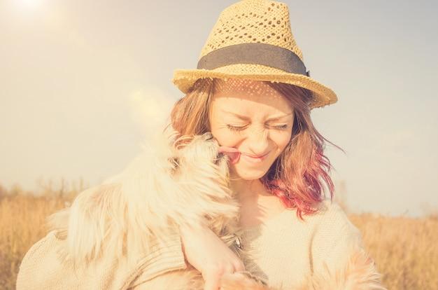 Il cane bianco sta baciando il suo proprietario in campagna - popolo caucasico - persone animali, natura e concetto di stile di vita