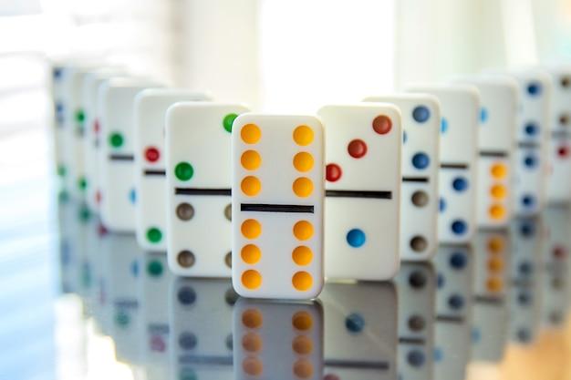 I domino bianchi stanno in fila sulla superficie dello specchio con il doppio sei che apre la strada