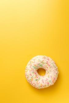 Ciambella bianca su sfondo giallo vista dall'alto copia spazio