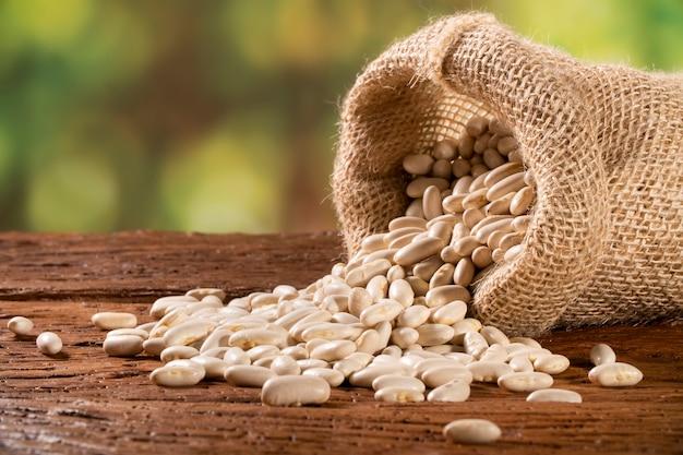 Fagioli bianchi essiccati fagioli nel sacco di iuta sul tavolo di legno, mucchio di legume concetto di fagioli.
