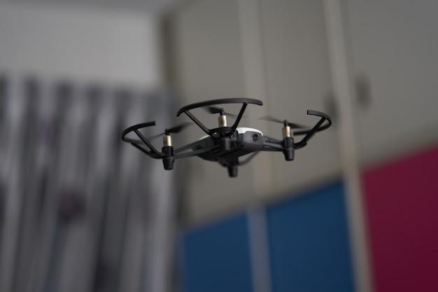 Il drone bianco vola nell'aria all'interno del residente che gioca con il motion blur o l'elicottero