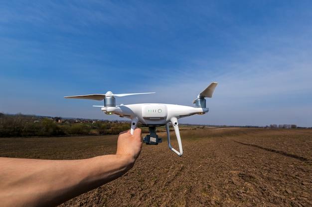 Il drone bianco in mano all'uomo isolato sullo sfondo del campo verde