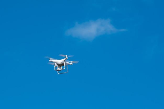 Drone bianco in bilico in un cielo blu brillante, elicottero radiocomandato con fotocamera.