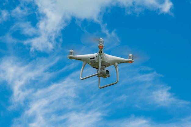 Drone bianco in bilico in un cielo blu brillante, elicottero radiocomandato