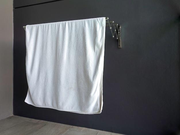 Asciugamano pulito a secco bianco appeso al portasciugamani sulla parete sulla terrazza