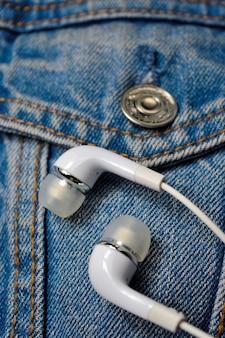 Auricolari bianchi sopra una giacca di jeans. avvicinamento.