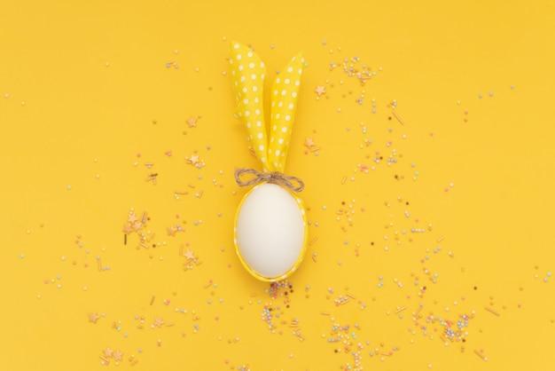 Uovo di pasqua bianco con orecchie di coniglio su sfondo giallo