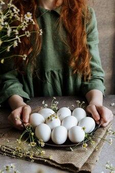 Le uova di pasqua bianche su una piastra di ferro sono decorate in stile rustico.