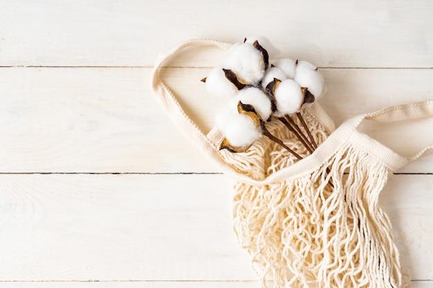 Struttura della maglia della borsa eco bianca con ramo di cotone su uno sfondo bianco in legno naturale.