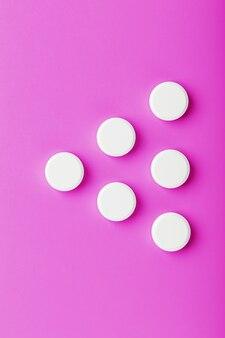 Pillole di ecstasy bianche in fila su una superficie rosa, isolare