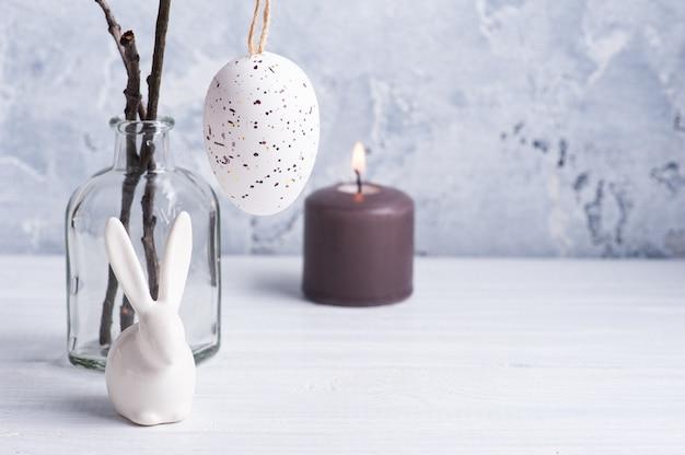 Uovo bianco e coniglietto nella composizione rustica di pasqua sulla tavola di legno bianca