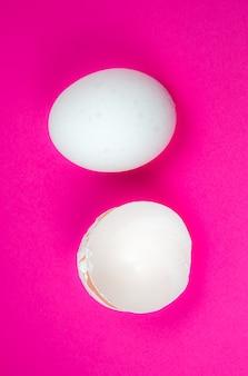 Uovo bianco e guscio d'uovo sullo sfondo rosa. copia spazio. minimalismo, foto originale e creativa. bella carta da parati. vacanze pasquali.