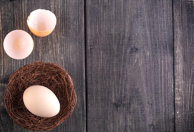 L'uovo bianco sul nido sul vecchio fondo di legno
