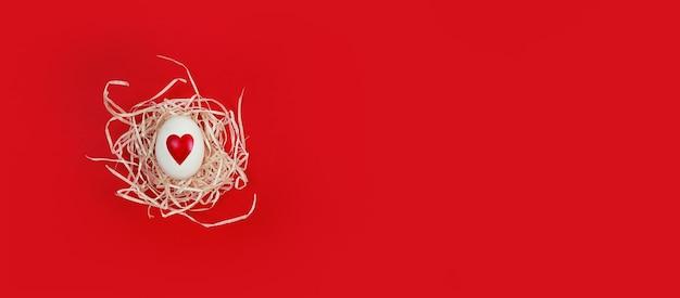 Uovo bianco a forma di cuore in nido decorativo su uno sfondo rosso con spazio di copia.