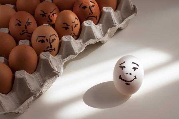 Uovo bianco con un sorriso dipinto e uova rosse con emozioni negative dipinte.